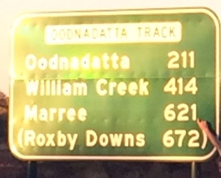 Road-sign showing destinations on Oodnadatta Track: Oodnadatta, 211; William Creek, 414; Marree, 621. Hand points to kms to Marree. Sign also notes turn-off to Roxby Downs, 672.