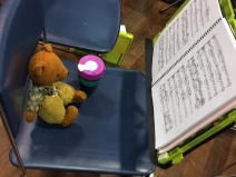 Viewed from side-on: Womble, a brown bear with light brown pants and vest and blue shirt, sits on a blue chair with a pink, teal and black KeepCup beside him. In front of him is an open music score on a music stand.