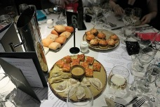 A table with white tablecloth is busy with menus, wine and water glasses, a table number and the entrees: a platter of mini burgers, a platter of varied bread rolls, and at the front, a platter of quiches and small dumplings and a bowl of dipping sauce.