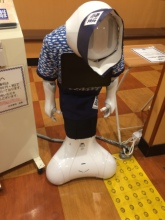Perspective shot of a robot wearing a uniform and sign, shut down for the night.